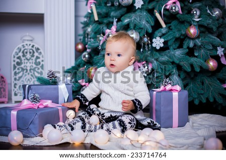 cute adorable baby girl sitting with christmas tree in interior with present boxes - stock photo