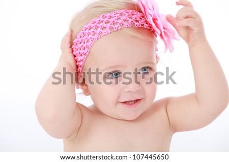 Cute adorable baby girl toddler with blond hair and blue eyes wearing pink head band with flower and naked happily smiling and playing on white seamless background - stock photo