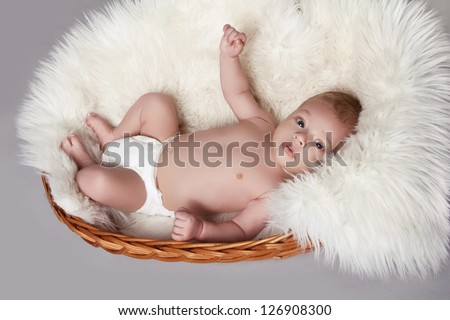 Cute adorable baby lying and smiling on grey background - stock photo