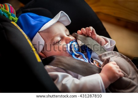 Cute, adorable baby taking a nap in his buggy, sucking a blue comforter. - stock photo