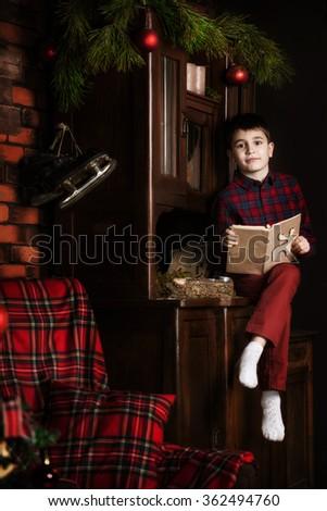 Cute adorable boy reading a book at christmas time. Cute adorable boy reading a book in front of the christmas tree, christmas time. - stock photo