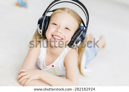Cute adorable girl wearing headphones and enjoying music - stock photo