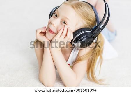 Cute adorable girl wearing headphones and enjoying music - stock photo