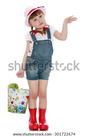 Cute adorable little blonde girl with pigtails in which braided the ribbons holding a large, filled to the brim with a bucket of apples. the head girls pink hat and on my feet red rubber boots. Girl - stock photo