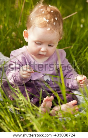 Cute adorable nice baby girl in green grass sitting under sakura tree
