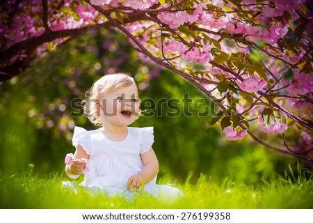 cute adorable nice baby girl in white spring dress smiling sitting under sakura tree - stock photo