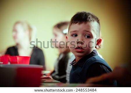 Cute adorable preschooler boy sitting in kindergarten looking confused.Sad child in kindergarten.Bored kid in preschool/kindergarten/nursery.Bored nervous boy at children birthday party - stock photo