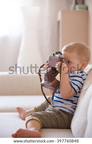 Cute adorable toddler boy sitting on the sofa in the living room and playing with vintage photo camera. Child taking picture with old camera. Future photographer. Kid with retro camera. - stock photo