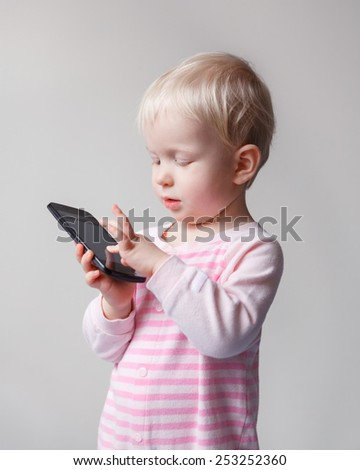 Cute adorable white Caucasian blond baby playing with mobile cell phone with funny expression on her face - stock photo