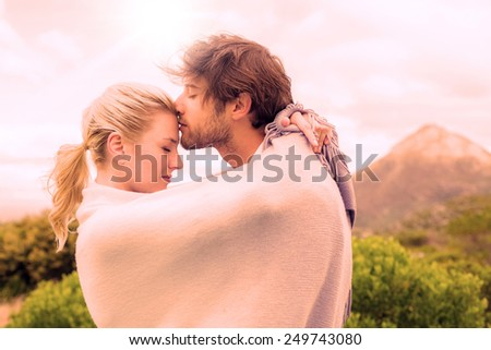 Cute affectionate couple standing outside wrapped in blanket on a chilly day - stock photo