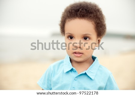 cute african american boy on a background of sand & sea - stock photo