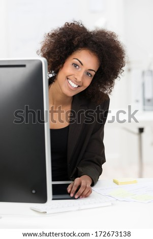 Cute African American businesswoman with a wild afro hairdo and friendly smile peering around her computer monitor at the camera - stock photo