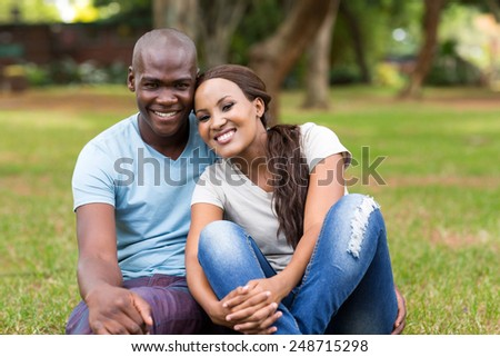 cute african american couple sitting on grass in the park - stock photo