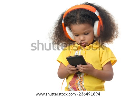Cute african american small girl listening to music on a cellphone using big orange headphones isolated on white - stock photo