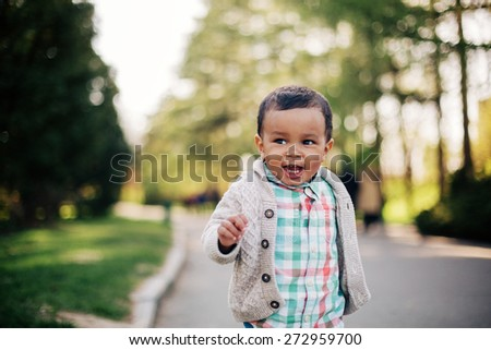 Cute african american toddler having fun outdoors in park. - stock photo