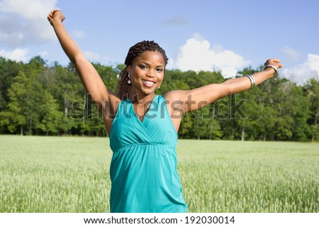 Cute African American woman smiling on a field - stock photo