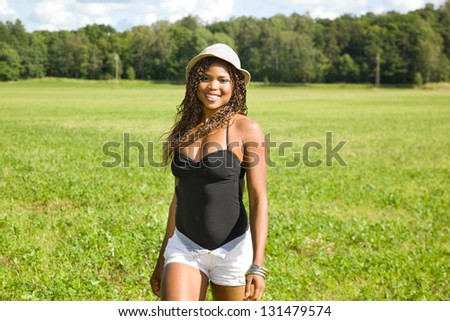 Cute African American woman walking on a field - stock photo