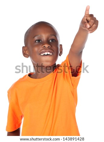 Cute african boy wearing a bright orange t-shirt. The boy is pointing with his finger and looking away from the camera. - stock photo