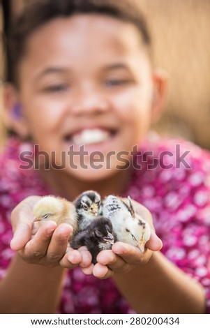 Cute African female child with baby chicks - stock photo