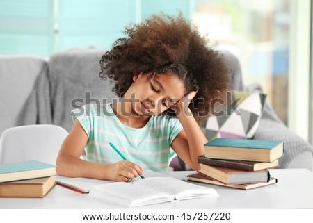Cute African girl doing homework - stock photo