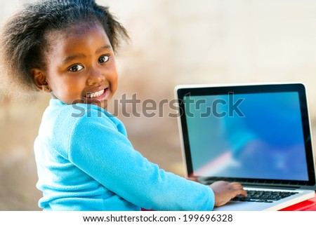 Cute African student working on laptop showing blank screen with copy space.