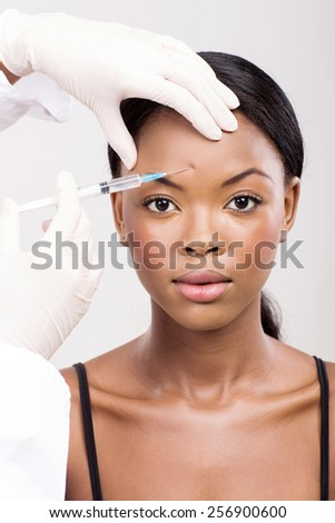 cute african woman receiving cosmetic injection on her forehead - stock photo
