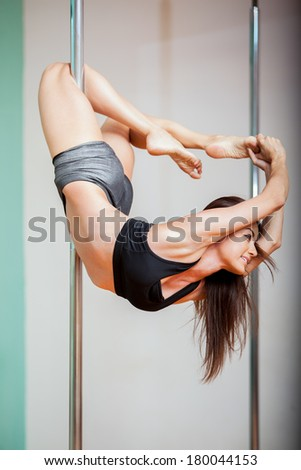 Cute and athletic Hispanic woman enjoying her pole dancing practice. Low angle of view