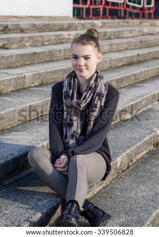 Cute and Beauty Caucasian Teenage Girl Posing Outdoors on Stairs. Vertical Image Orientation - stock photo