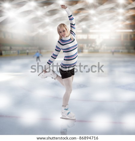 cute and blond girl with shorts and a nice sweater making a ice skating figure