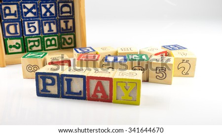 Cute and colourful wooden block forming word PLAY. Concept of fun education. Isolated on white background. Slightly de-focused and close-up shot. Copy space. - stock photo