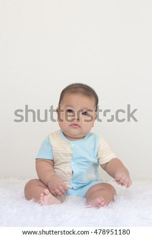 cute and fat asian baby sitting on the floor.