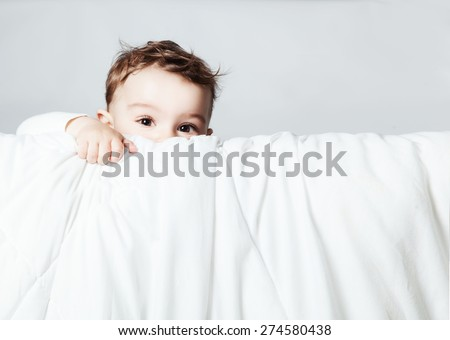 Cute and funny baby is looking and climbing on blanket over white background. Copy space. - stock photo