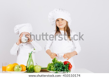 Cute and funny little kids with fruit and vegetables in the kitchen white background