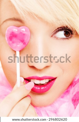 Cute and funny pink make up portrait close up. Lollipop and vivid pink lipstick. Platinum blonde.