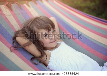 Cute and happy girl lying on a hammock  - stock photo