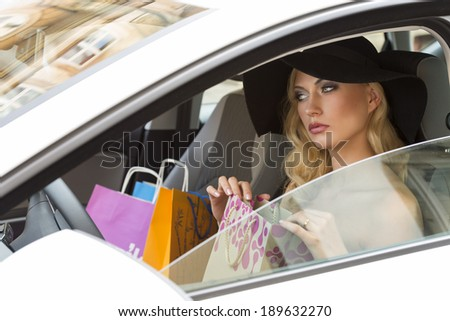 cute and sensual blond woman very elegant ,sitting in car with shopping bags in hand - stock photo