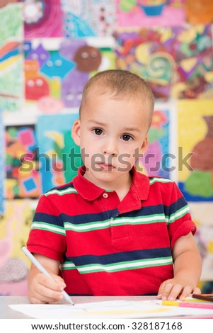 Cute and serious toddler boy is at the Art class. Painting with gray felt pen and looking at the camera. Colorful wall in background. - stock photo