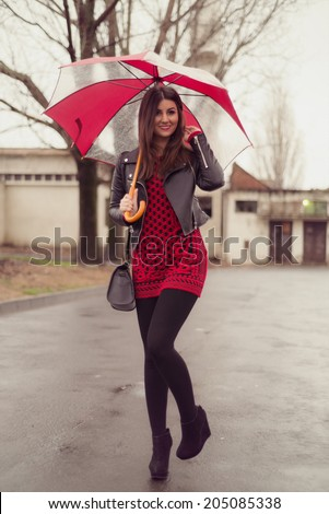 Cute and sexy woman posing in the rain holding an umbrella and wearing a red knit sweater dress with flower wisteria print over black tights leggings  - stock photo