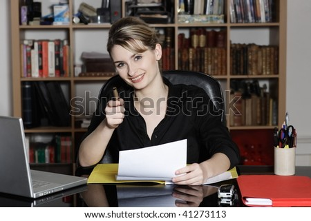 cute and smiling businesswoman at the office desk pointing his pen as his finger at you - stock photo