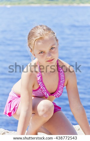 Cute angry girl on the riverbank in pink swimsuit