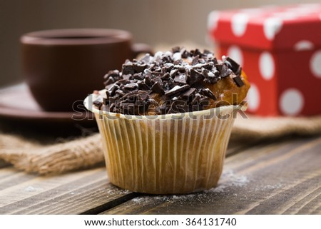 Cute appetizing muffin with chocolate crust in paper form homemade pastry dessert treat for holiday in background of brown cup and saucer bright red box on wooden table indoor closeup, horizontal  - stock photo