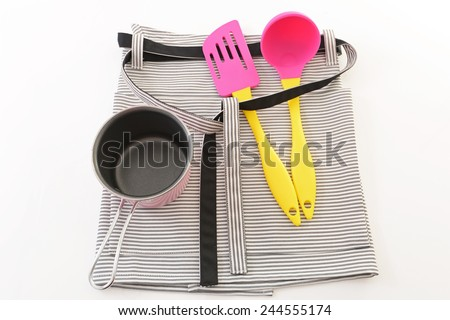 Cute apron and kitchen supplies - stock photo