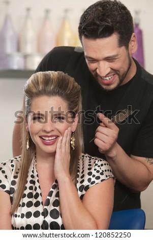 Cute Arab hair stylist admiring woman's haircut - stock photo