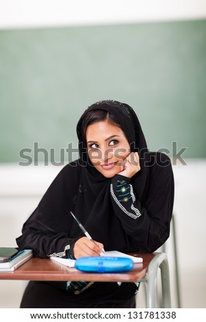 cute Arabic high schoolgirl in classroom - stock photo