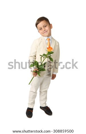 Cute Arabic looking little boy in elegant three-piece suit stands lovely smiling with rose flower in hand - full height portrait isolated on white background - stock photo