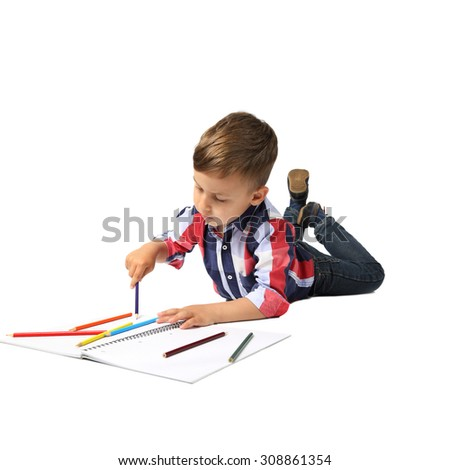 Cute Arabic looking little boy lies on floor drawing with color pencils isolated on square white background