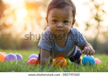 Cute asian baby crawling in the green grass and colorful ball - Sunset filter effect - stock photo