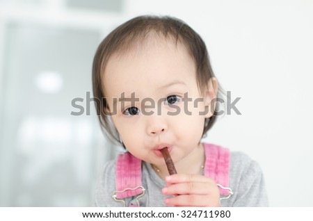 Cute Asian baby drinking from straw at home.