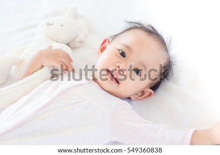 Cute asian baby girl lying on the bed and playing with a toy bunny