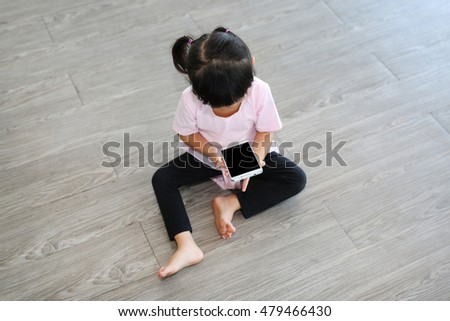 Cute asian baby girl playing a smartphone